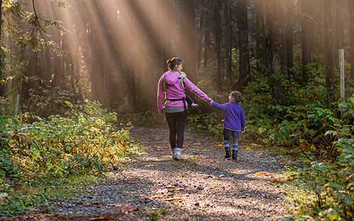 Adult and child walking a path together
