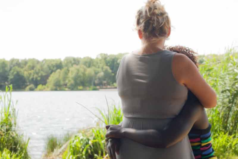 parent and child hugging and looking over water
